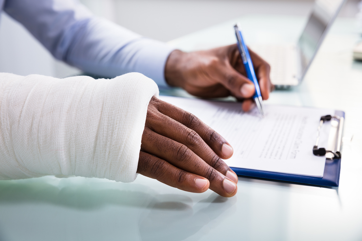 Injured Man Filling Workers' Compensation Insurance Claim Form